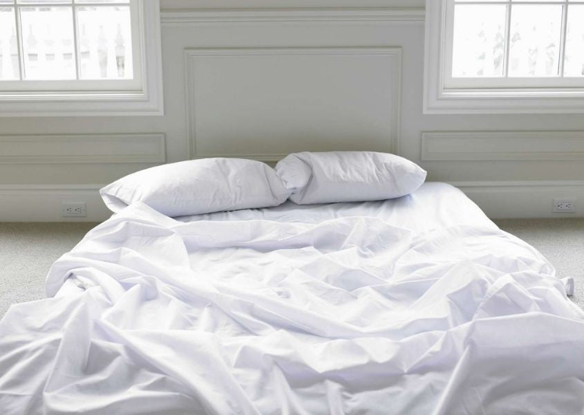 mattress on the floor with white covers