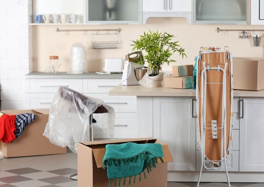 kitchen with moving boxes and iron board for tips to prepare for an easy house move blog