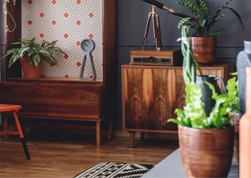 Terracotta plant plot and green plant with wooden sideboard against dark blue wall