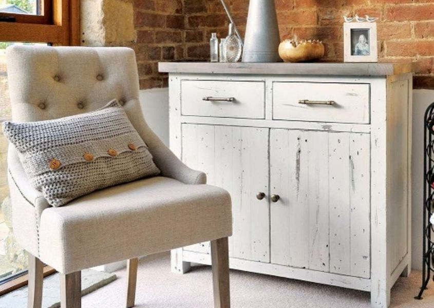 Cream fabric armchair in front of white wooden sideboard