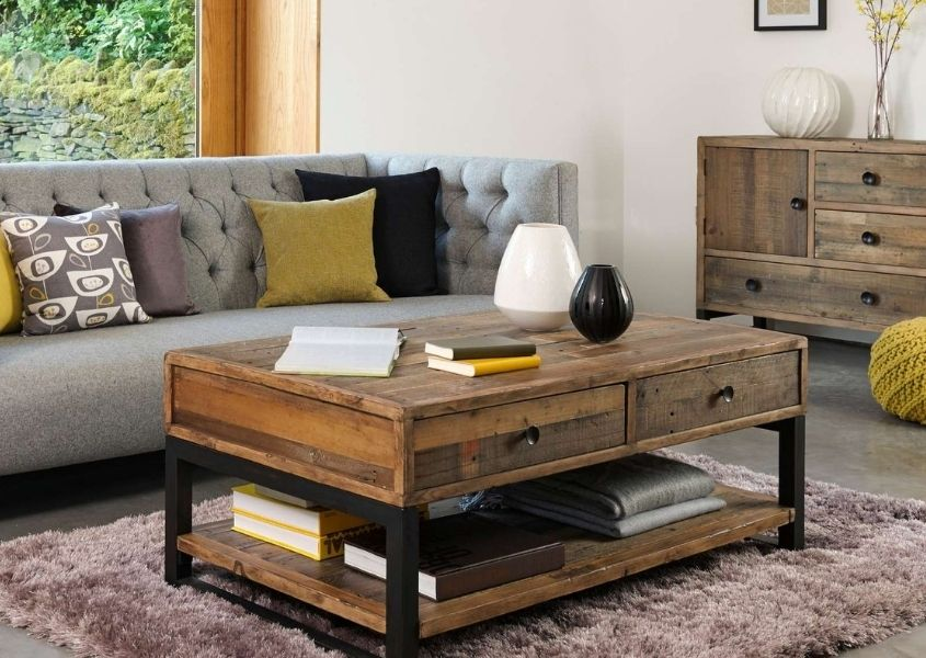 Industrial coffee table on rug with grey sofa and reclaimed wood sideboard in background