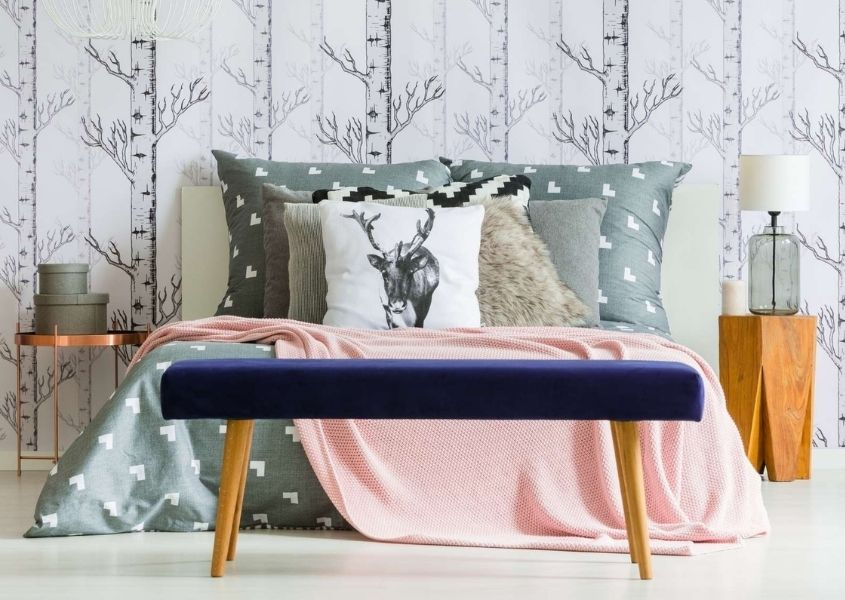 Purple velvet foot stool and large king size bed with grey headboard