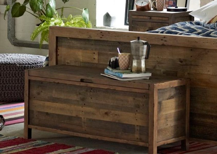 Reclaimed wood blanket box next to wooden bed frame