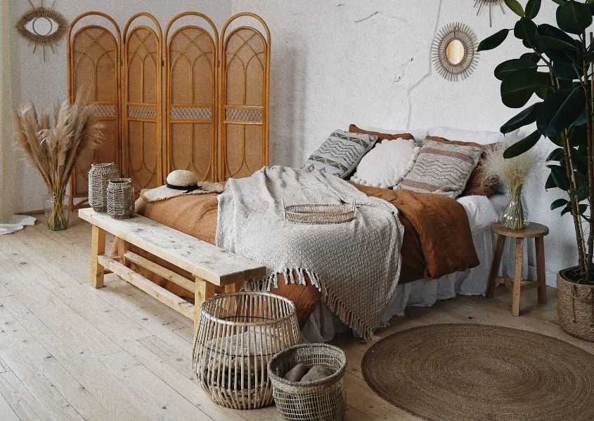 Wooden bench at bottom of double bed in boho style