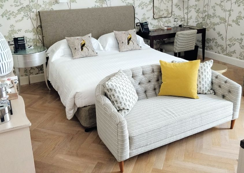 Small grey sofa at foot of a double bed with white covers