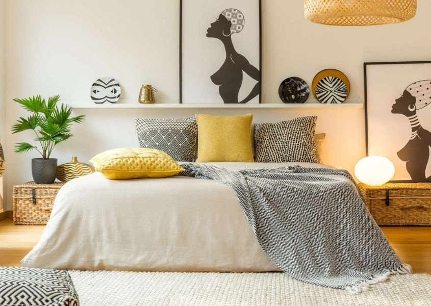 Bedroom featuring large bed with light and dark grey covers and cushions and artwork on the wall