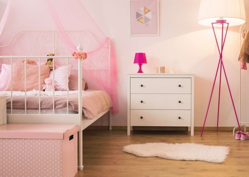 Pink children's bedroom with white metal bed, white chest of drawers and sheepskin rug on wooden floor