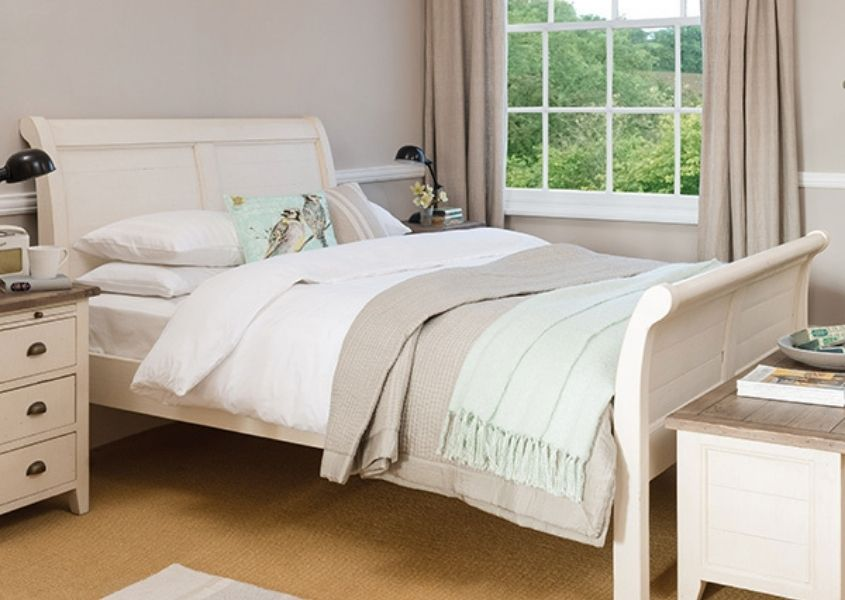 White wooden king size bed with white covers, white painted bedside table and blanket box and beige curtains