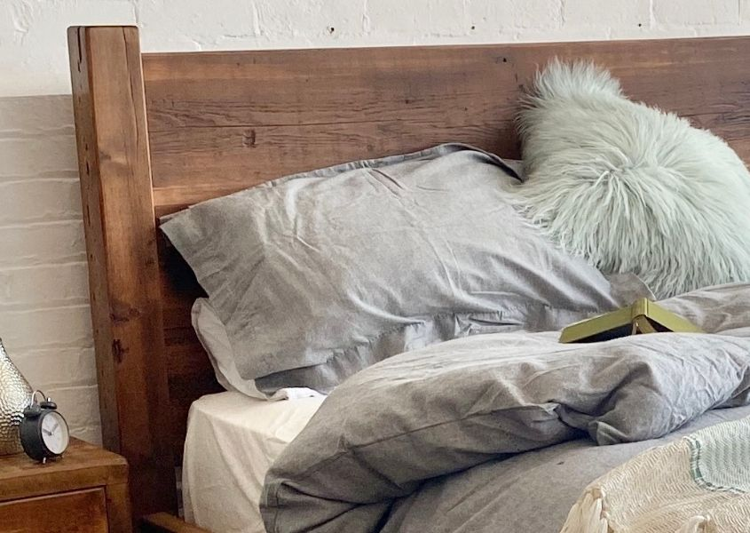 reclaimed wooden headboard with grey covers