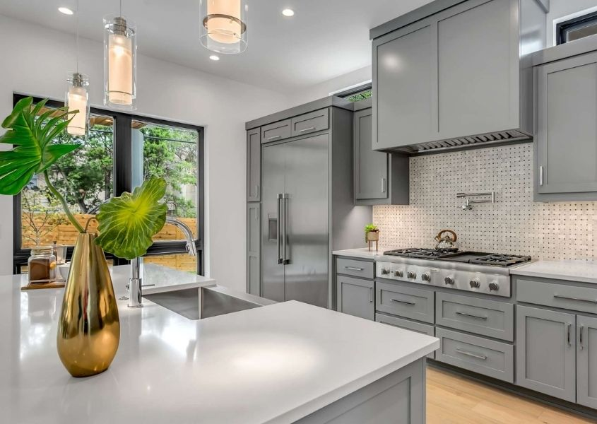 Grey modern kitchen with white stone worktops and gold vase with large green tropical leaf on top