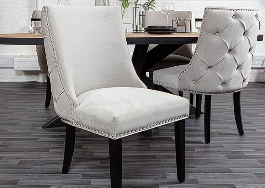 grey upholstered dining chair with button studded back and black wooden legs