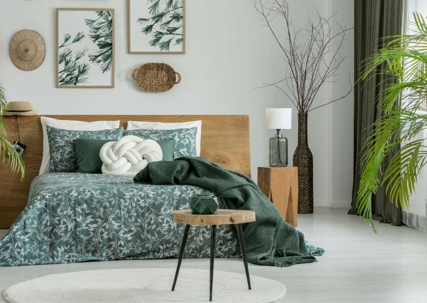Bedroom with wooden bed and green covers, green curtains and green plants