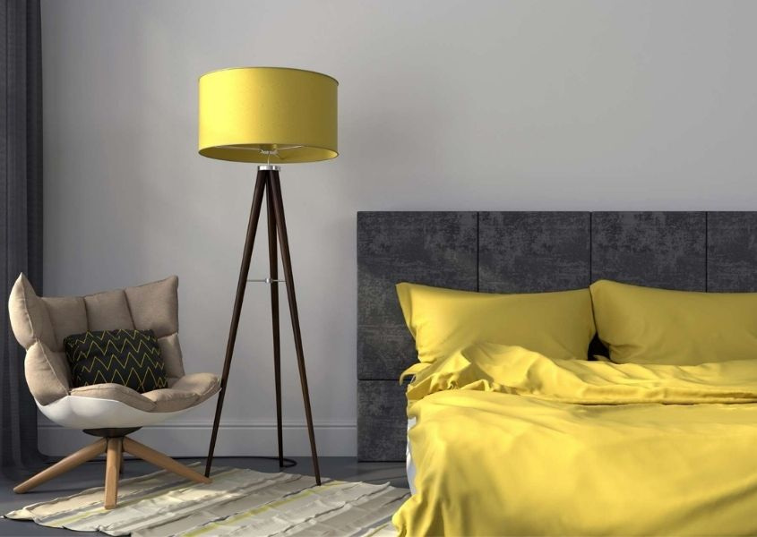 Bedroom with grey upholstered bed and bright yellow covers and yellow floor lamp