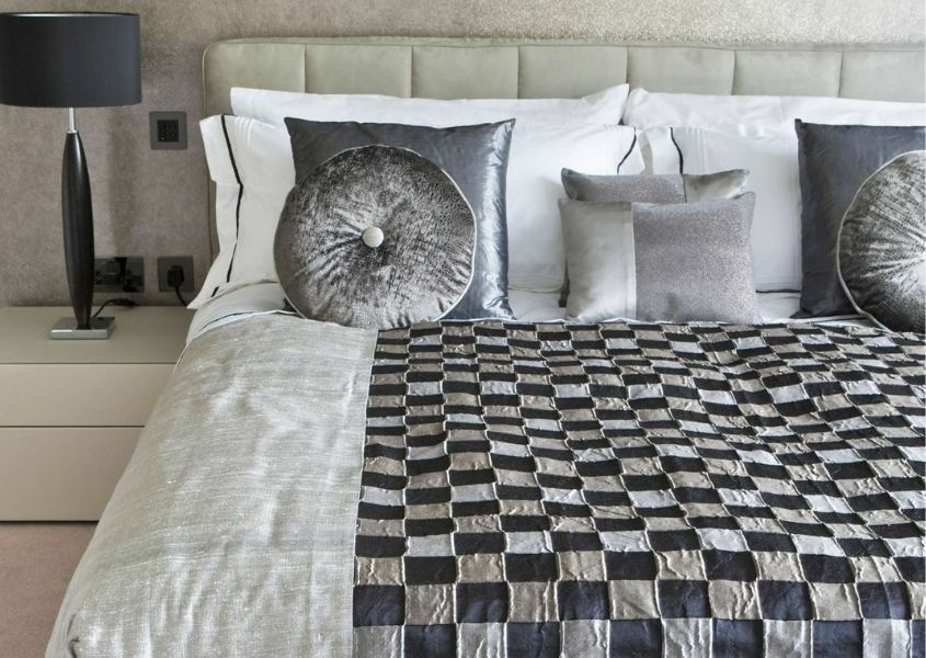 Close up of silver bed covers and cushions with chequered bed throw