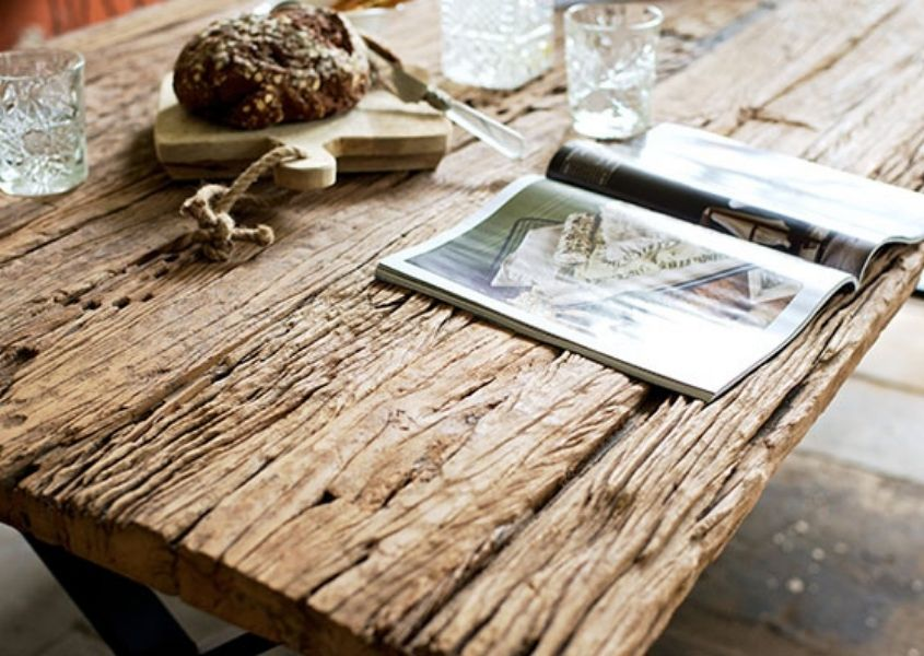 Close up of rustic reclaimed wood dining table with open magazine on top