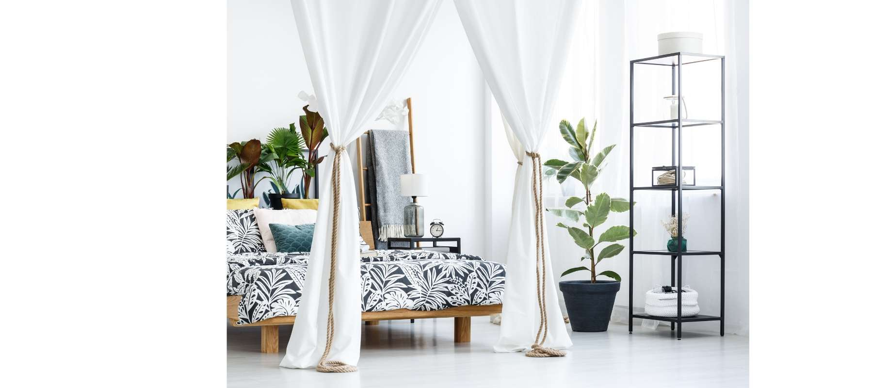 White four poster bed with green plants and industrial bookcase