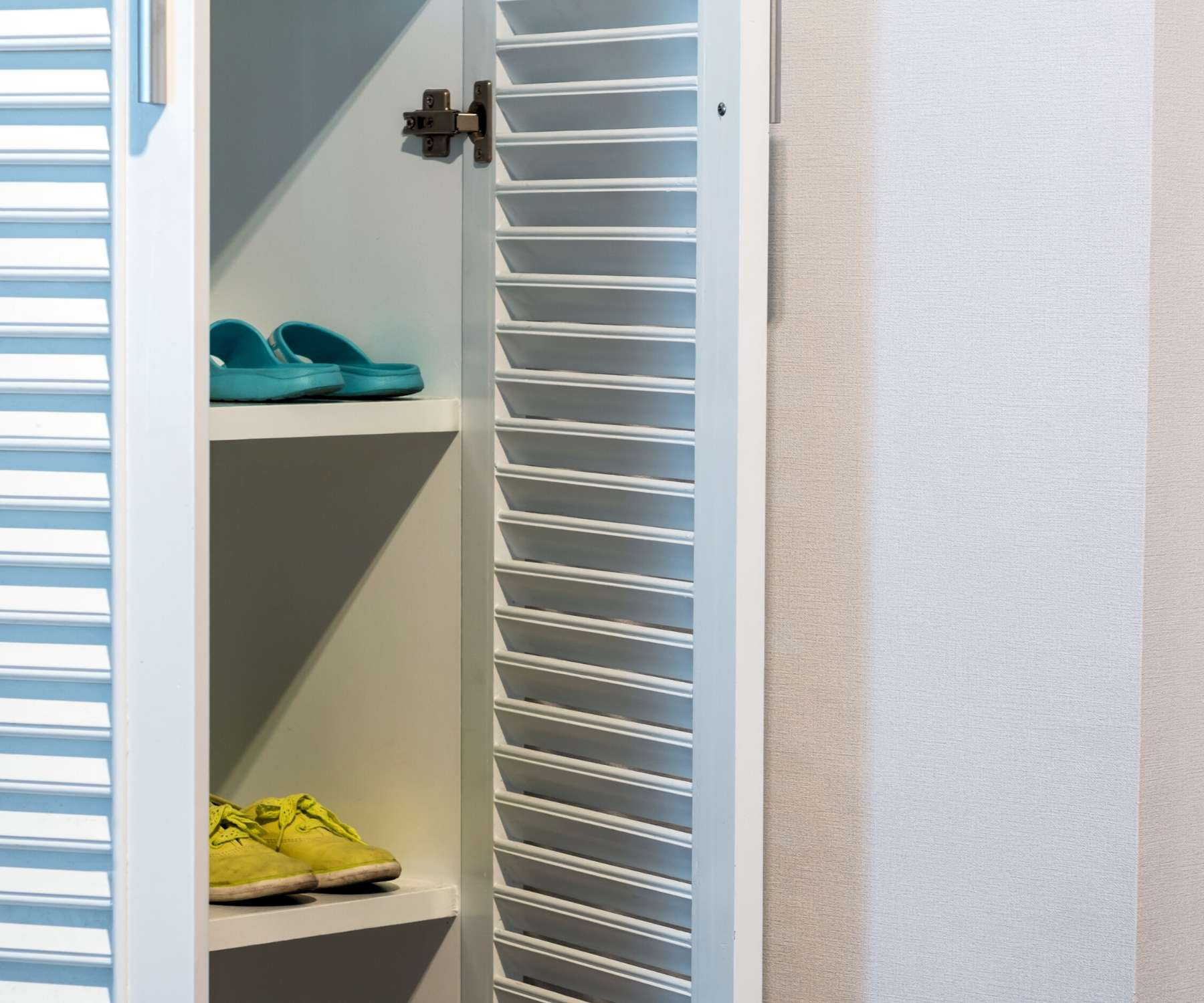 white wooden storage unit with louvered doors