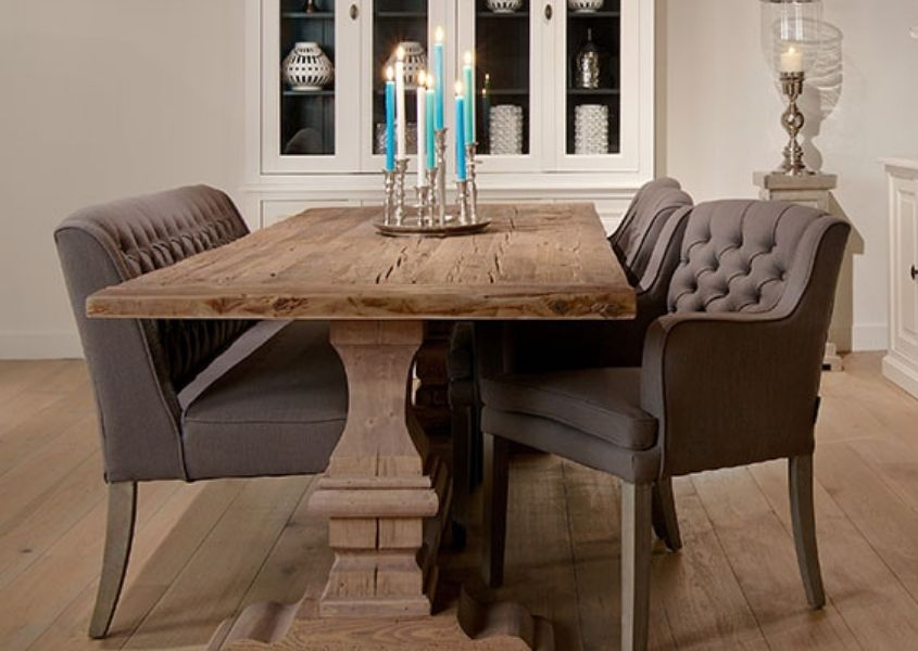 Reclaimed wood dining table with pedestal leg and grey fabric armchairs