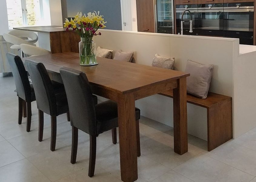Wooden table and dining bench against kitchen island with grey chairs
