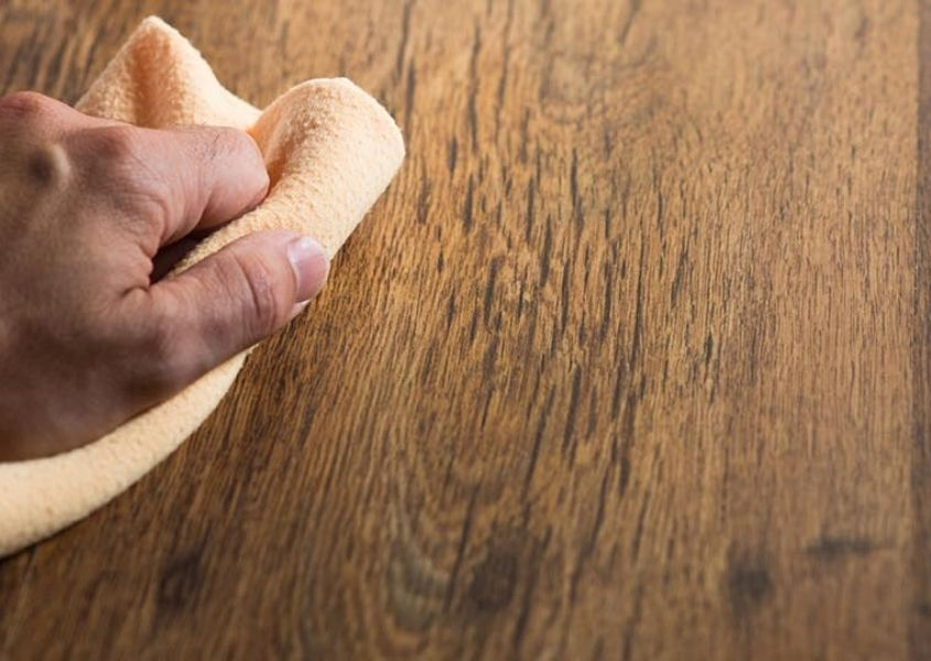 Close up of rustic wood with hand wiping wood with cloth