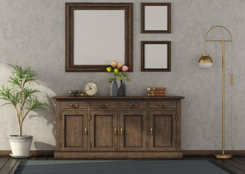 Wooden sideboard with trio of mirrors on wall above and a gold floor lamp and plant in room