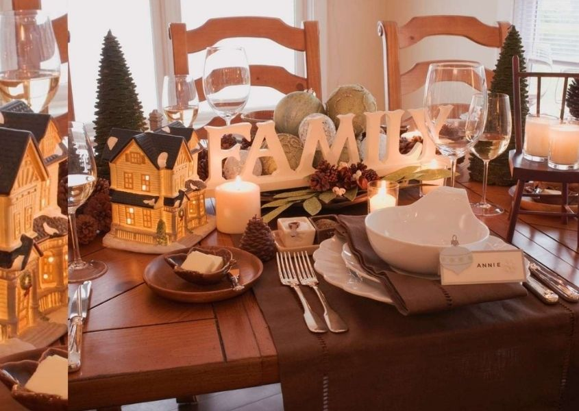 Wooden dining table decorated with christmas decorations and wooden sign spelling family