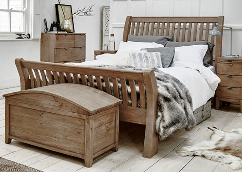Bedroom with reclaimed wood bed and faux fur covers with wooden blanket box