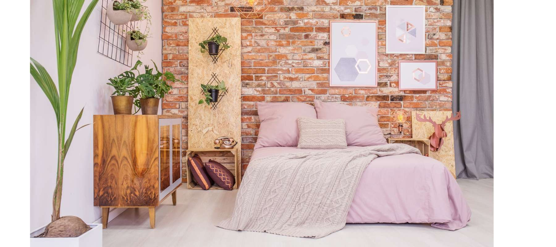 Double bed with blush pink covers against an exposed brick wall
