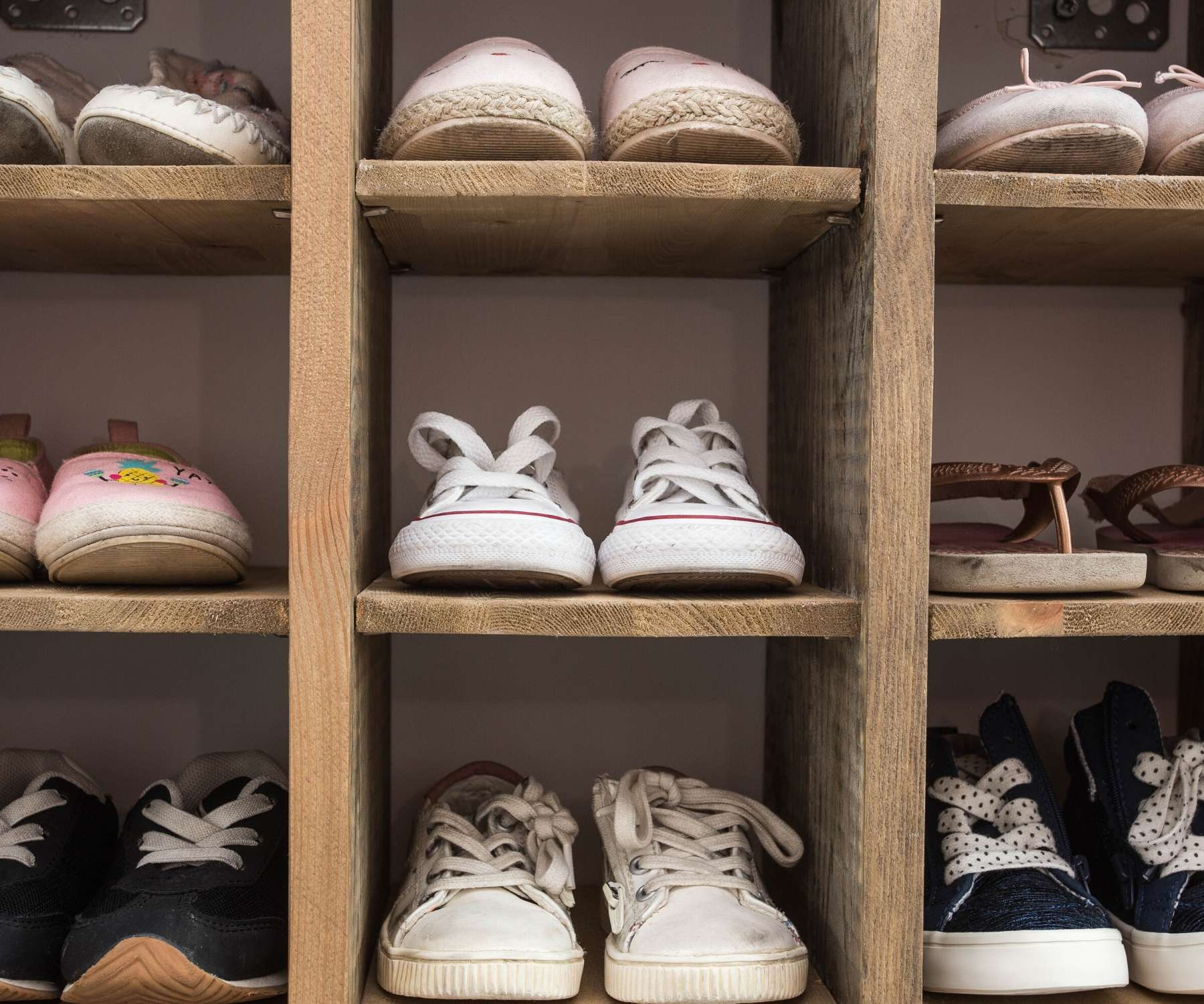 wooden shoe storage unit with shoes in it