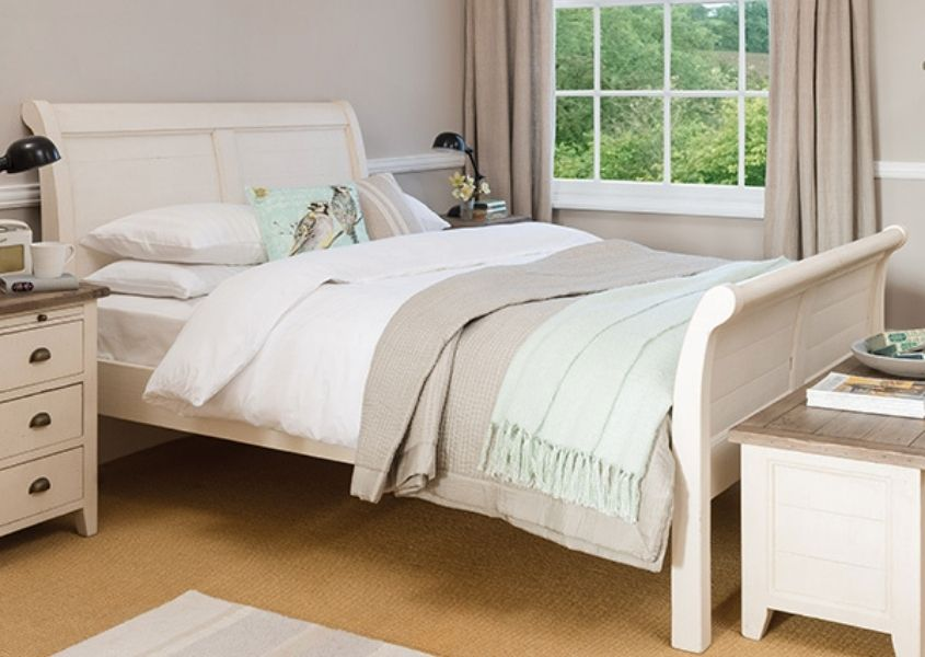White reclaimed wood sleigh bed with matching bedside table and blanket box