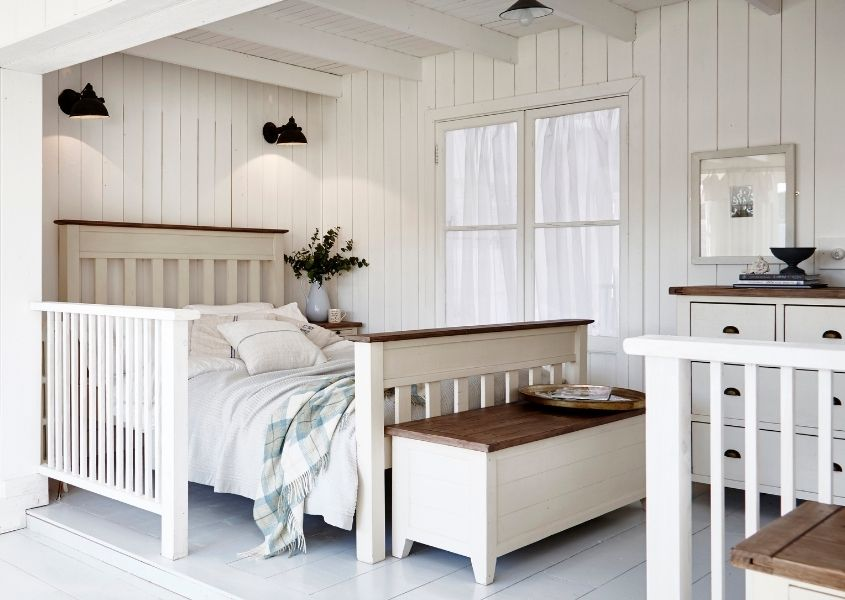 White painted reclaimed wood bed in white wood panelled bedroom with matching wooden blanket box and black spot lights on wall behind bed