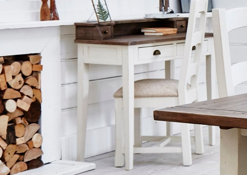 White painted reclaimed wood writing desk with natural wood top, next to pile of logs in fireplace