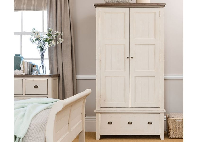 Bedroom with white double wardrobe with drawers and end of a white double bed