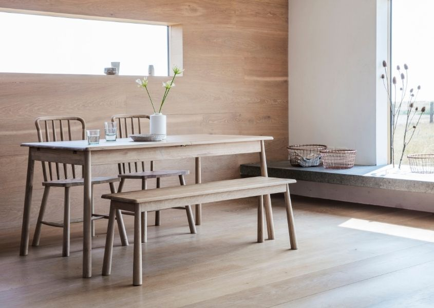 Pale wooden dining table with wooden bench in room with wood wall and floor