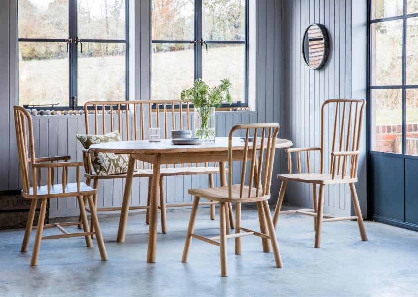 Pale wood dining table with matching spindle chairs in bright dining room with dark blue doors