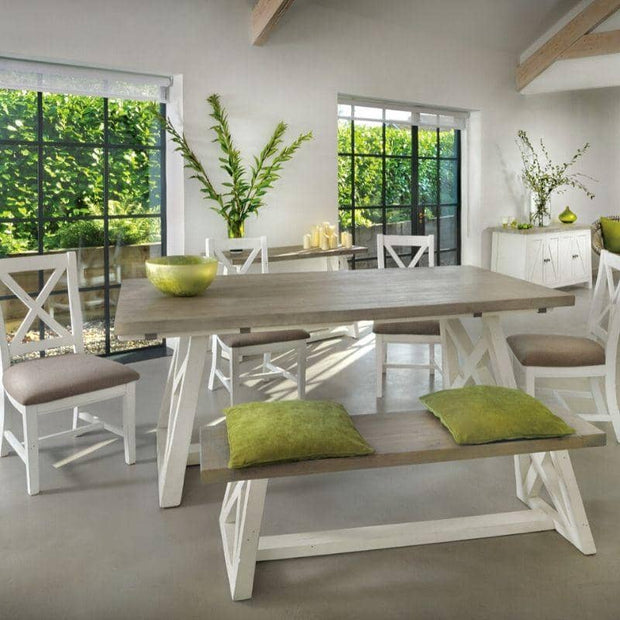 White painted Abingdon Reclaimed Wood Trestle Dining Table with bench, green cushions and plant in background