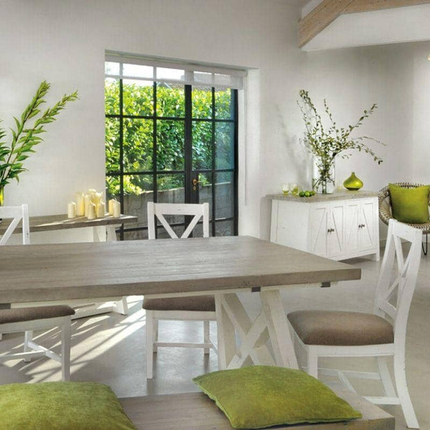 White painted Abingdon Reclaimed Wood Trestle Dining Table with chairs and green cushion