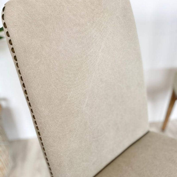 Close up of linen fabric on cement coloured ambrose dining chairs