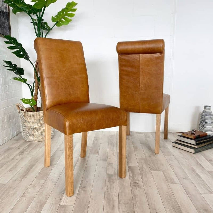 Pair of leather roll back chairs with plant and books in background