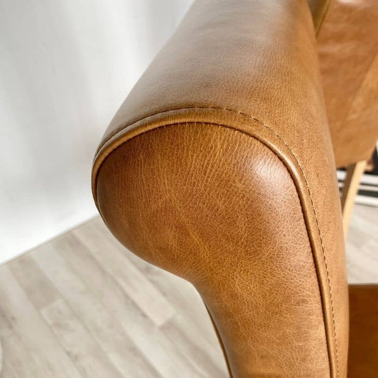 Close up of leather stitching and curve of back of roll back chair
