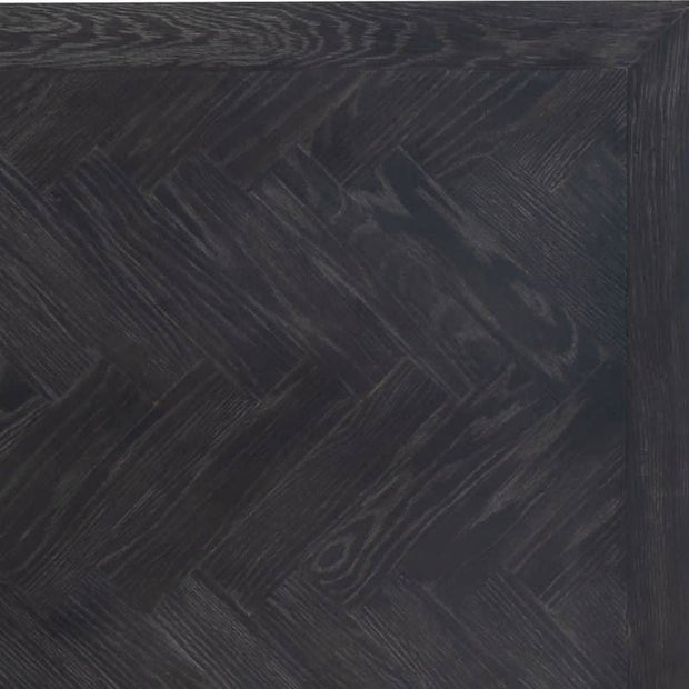 Zoomed in photograph of Blackbone industrial oak desk, Showing the herringbone pattern and natural grain in the dark oak wood.