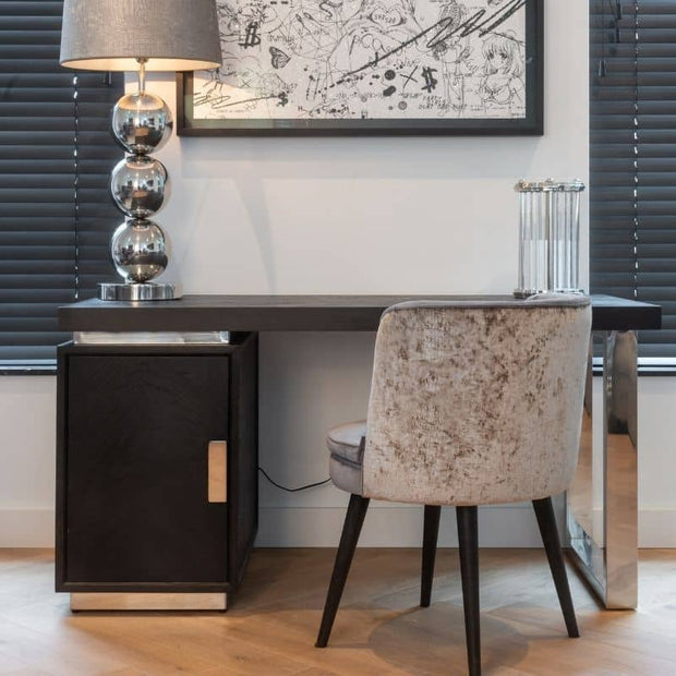 Lifestyle photograph of Blackbone industrial oak desk, styled with grey velvet chair and silver lamp.