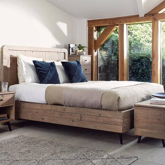 Pale reclaimed wood bed frame with blue cushions