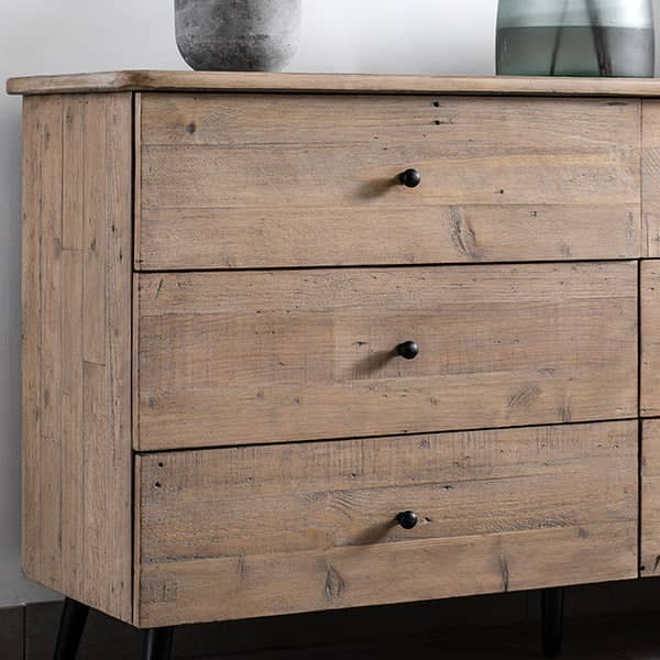 A reclaimed wooden chest of drawers with black rounded handles