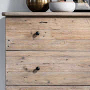 Close up of reclaimed wood chest of drawers with black knobs