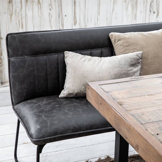 Close up of faux leather dining bench with cushions