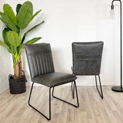 Two Cleo Faux Leather Dining Chairs in Grey with plant
