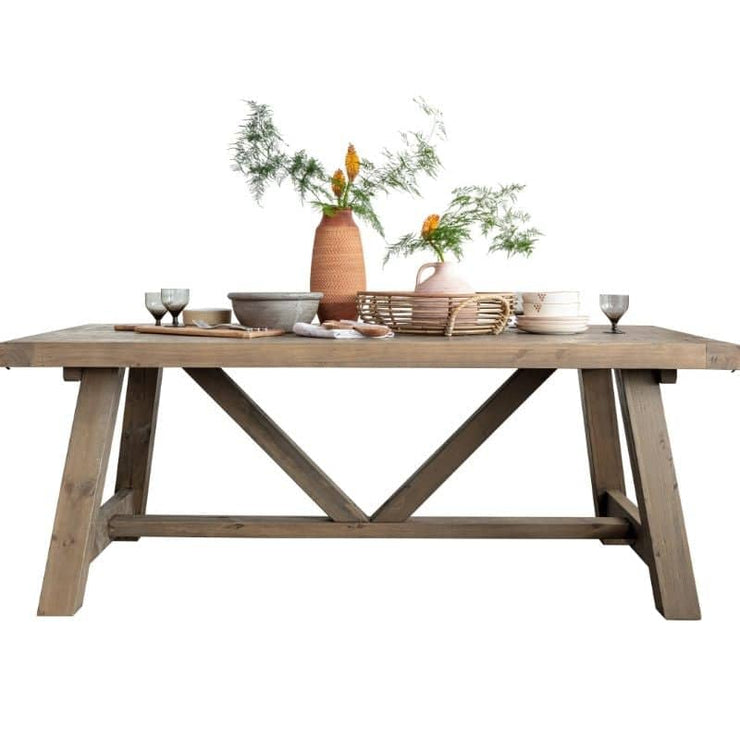 Cut-out photograph on white background on Farringdonreclaimed wood extendable trestle dining table. Image shows A-frame legs, table styled with terracotta pots and plants.