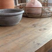 Lifestyle photograph close-up of Farringdon trestle extendable dining table. Image shows knots and pits, characteristic of reclaimed wood, styled with crockery in warm tones.