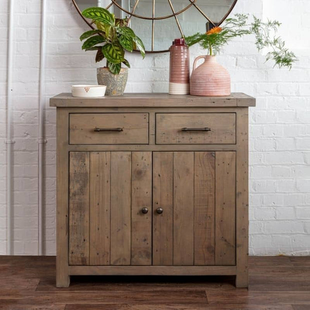 Lifestyle photograph of Farringdon reclaimed wood medium sideboard. image shows two drawers with cupboard beneath, styled with plant pots in warm tones.